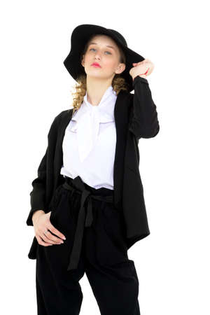 Elegant lady in black suit touching her hat Фото со стока