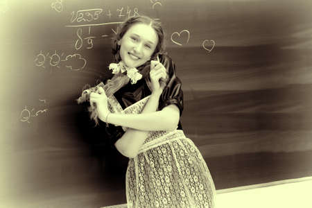 Retro shot of joyful school girl in uniform Фото со стока