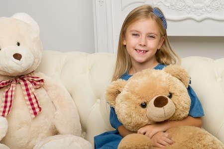 Girl sitting on sofa hugging teddy bear