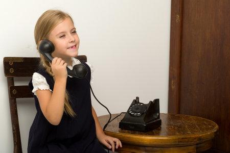 Cute blonde girl talking on vintage telephone