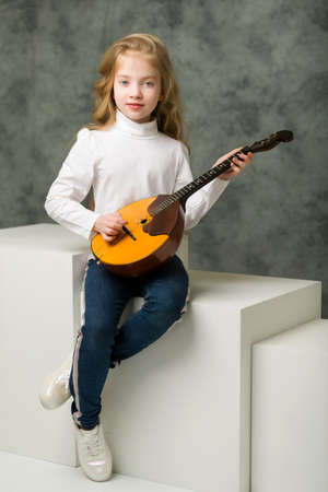 Cute little girl is playing dombra.