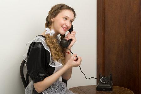 Girl in retro school uniform sitting on chair