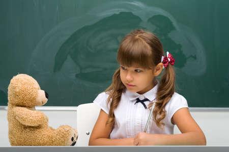Cute schoolgirl sitting at desk and writing Фото со стока