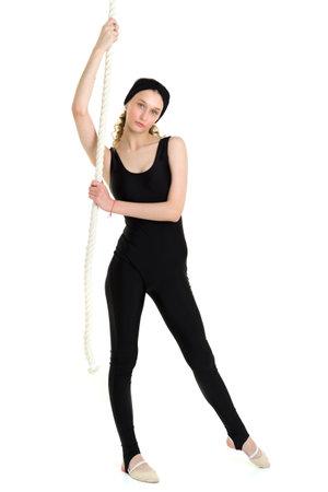 Slim teenage girl gymnast training with rope swing Фото со стока