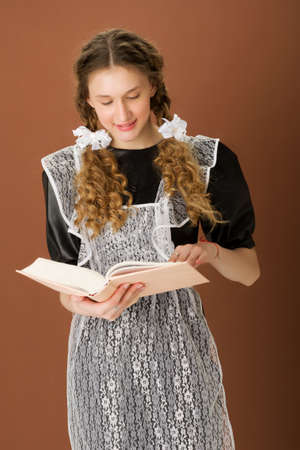 Pretty braided teen girl reading book with smile
