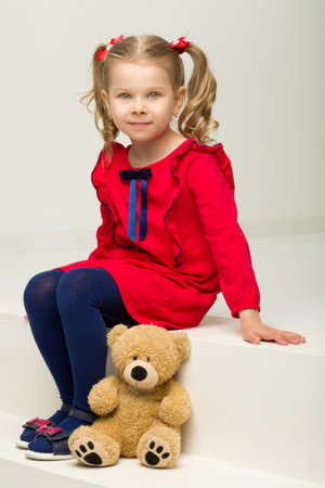 Little girl sitting on stairs with teddy bear