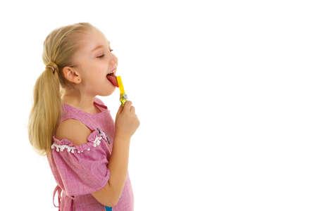 Cute little girl licks a candy.