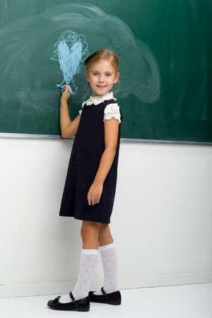 Back view of girl drawing with chalk on blackboard Фото со стока