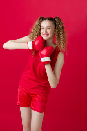 Pretty teen girl fighting with red boxing gloves