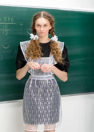 Portrait of school girl in front of blackboard