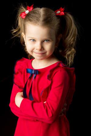 Cute blonde little girl standing on black backdrop Фото со стока