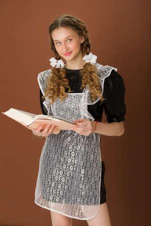 Pretty girl in retro school uniform reading book