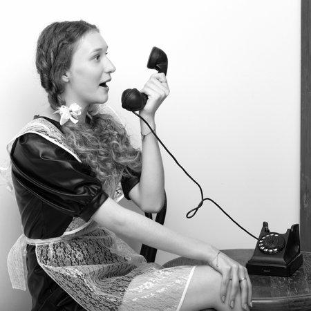 Emotional pretty school girl talk by vintage phone