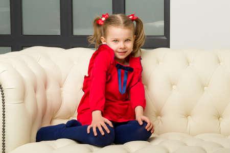 Cute blonde little girl sitting on comfy armchair Фото со стока