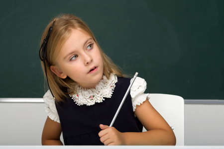 Girl thinking while sitting at desk at lesson Фото со стока