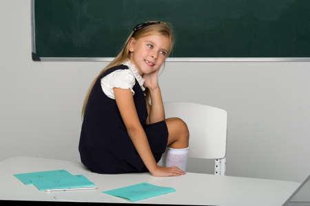 Adorable schoolgirl sitting on desk in classroom