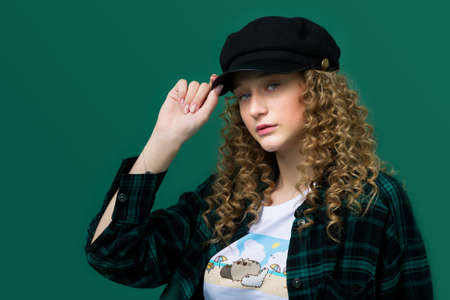 Portrait of stylish pretty girl touching black cap