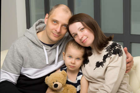 Parents and their little daughter sitting on sofa Фото со стока