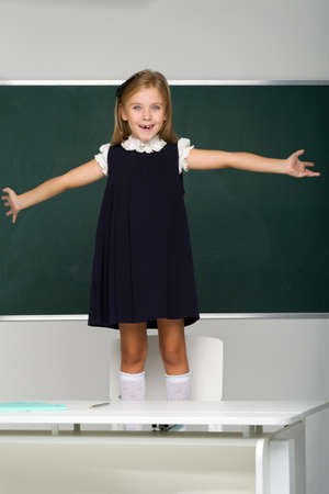 Smiling blonde female student in school uniform stands on a chair in front of the blackboard. School and education concept