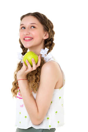 Smiling girl with two braids holding green apple Фото со стока