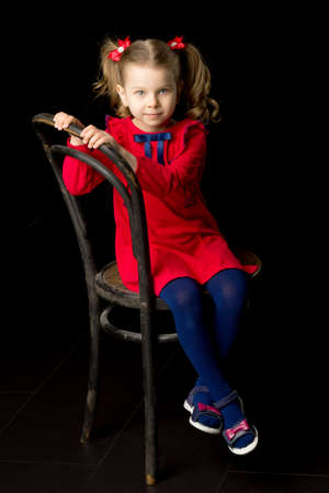 Cute blonde little girl sitting on wooden chair