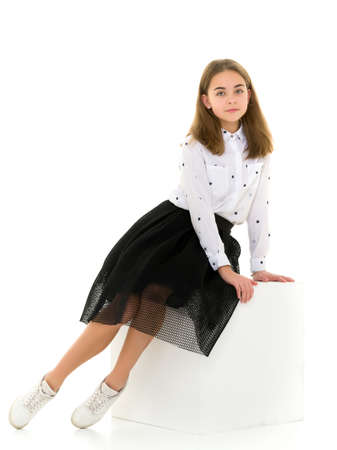 Adorable Smiling Girl Sitting on White Cube and Gesturing Фото со стока