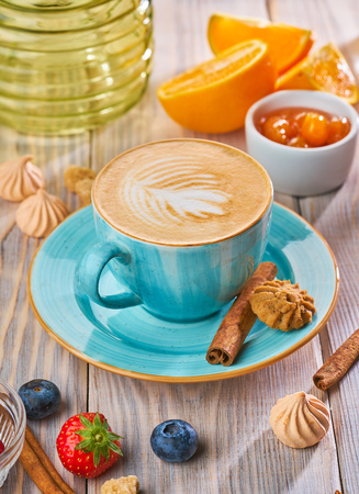 Cappuccino in a blue cup with biscuit cookies on a rustic wooden table