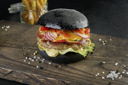 Black burger on rustic wooden board on black background.