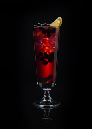 Alcoholic cocktail with black currant on black background