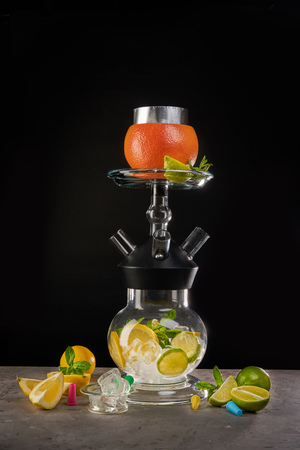 Modern glass hookah with citrus fruit aroma in black background