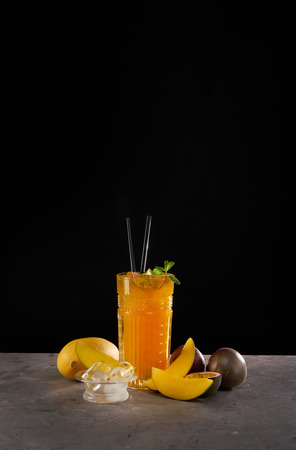 Fresh cocktail with mango, mint, passion fruit and ice. Alcoholic, non-alcoholic drink-beverage on black background