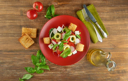 Fresh healthy salad on red plate and basil leaves on wooden table. View from above