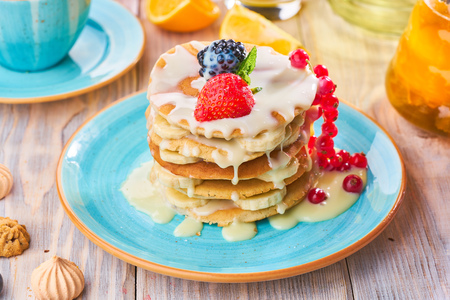 Stack of homemade pancakes with strawberrie, banana and red currant on a blue plate 写真素材