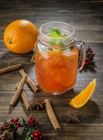 orange coctail in the glass jar on wooden table with cinnamon Stockfoto