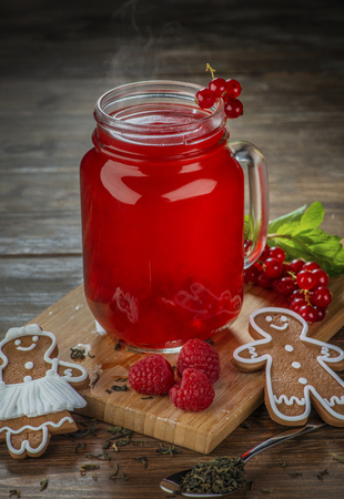 glass jar with delicious healthy hot raspberry tea and gingerbread man