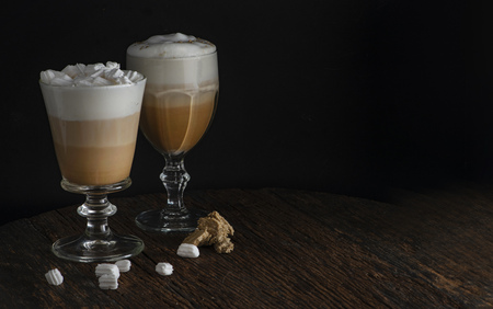 Latte coffee with tasty foam in glass with marshmallow on dark rustic table over black background