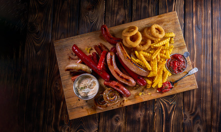 Delicious snacks with grilled sausages, fried potato, onion rings and two glasses of beer on wooden board in rustic wooden table. Top view