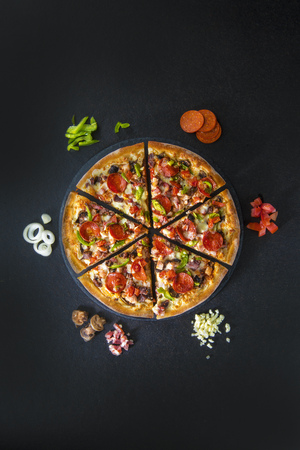 Tasty sliced pizza with raw ingredients on black background. Top view 写真素材