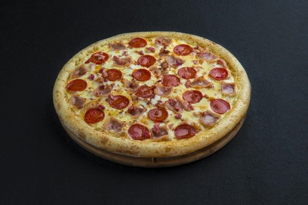 Hot homemade pepperoni pizza ready to eat on black background 写真素材
