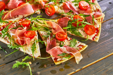 Italian pizza with ham, tomatoes, cheese and herbs on vintage wooden background.