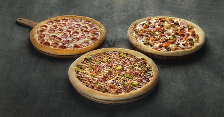 Three pizzas on a dark wooden background