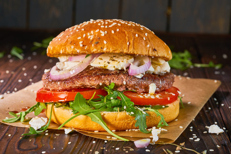 Home made beef burger with arugula and tomatoes served on wooden background