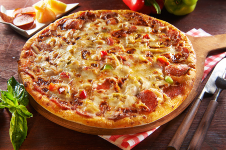 Fresh pizza on wooden table with ingredients