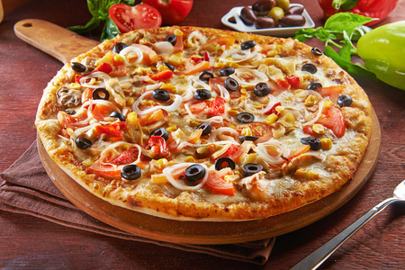 whole italian pizza on wooden table with ingredients 写真素材