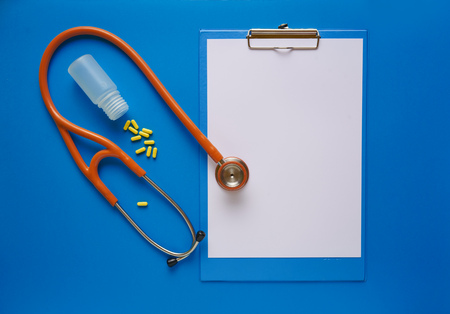 Pharmacy background. Tablets and Stethoscope on a blue background. Copy space for a text.