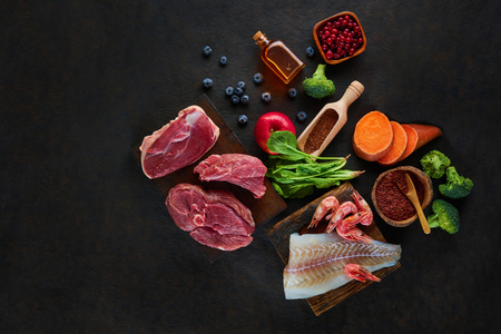 Fresh organic ingredients for cooking on dark background. Top view, place for text.