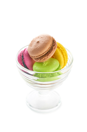 Colorful french macaroons in glass bowl on white background