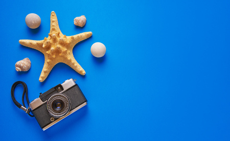 starfish, seashells and film camera on blue background. Flat lay. Top view.