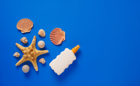 Flat lay concept of summer travel vacations. Top view of seashells and starfish on blue background with sunscreen bottle