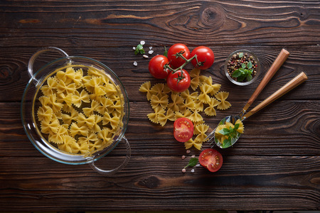 Dry farfalle pasta, fresh tomatoes and basil served with sea salt on wooden background. Top view, flat lay 写真素材